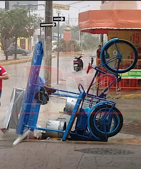 Tamale lady's cart tipped over in rain and wind.
